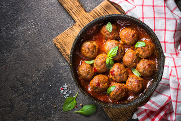 Meatballs in tomato sauce in a frying pan on dark stone table.