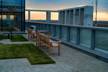 Modern rooftop patio with wooden benches in evening