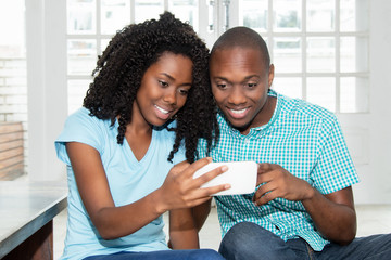 African american couple watching tv online on phone