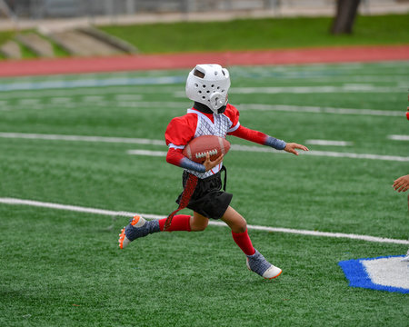 Little boys and girls playing flag football