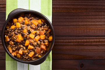 Homemade chili con carne with mincemeat, red and black beans, tomato sauce and pumpkin in rustic bowl, photographed overhead with copy space on the side (Selective Focus, Focus on the chili)