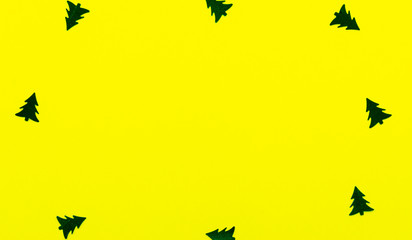 Background Christmas decoration-christmas trees,stars on a yellow background and copy space.