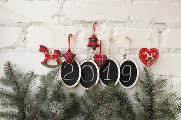 New Year or Christmas background. Figures 2019, fir branches and traditional decorative elements.