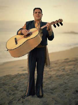 mariachi man on the beach playing the guitar.