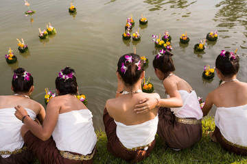 Woman floating krathong in water