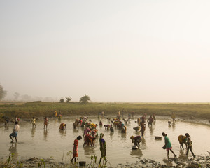 People in large mud puddle