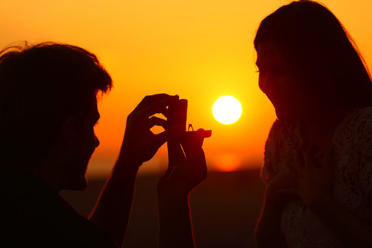 Marriage proposal at sunset with sun in background