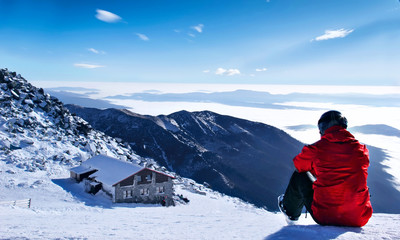 Winter lanscape mountains.Skier siting on the snow on the first plan and mountain house on the second plan.Chopok, Slovakia