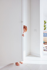 happy toddler baby boy playing hide and seek game, hiding himself behind the cabinet door, candid lifestyle