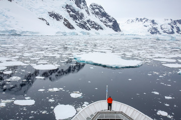 Person on a boat over looking icebergs and mountains