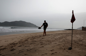 A man walks past a red flag, warning of dangerous conditions, along a closed beach in Mazatlan as Hurricane Willa approaches the Pacific beach resort, Mexico