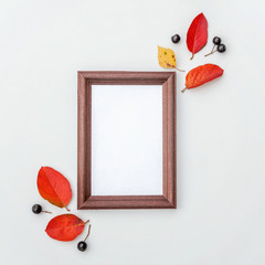 Autumn floral composition. Photo frame, chokeberry rowan berries, colorful leaves on white background. Autumn fall natural plants ecology fresh wallpaper concept. Flat lay, top view, copy space