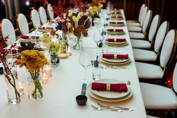 table setting in a restaurant decorated with napkins on plates and flowers and candles