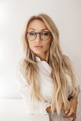 Beautiful woman with fashionable glasses in the stylish white shirt near the gray wall in the studio
