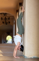 Female Yoga Instructor Doing a Headstand Against a Wall