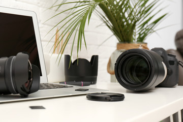 Laptop and professional photographer's equipment on table indoors