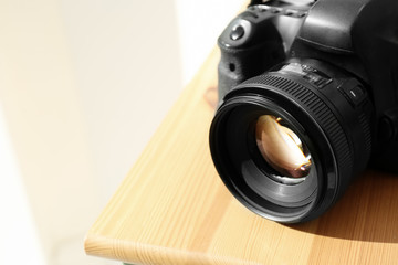 Professional camera on wooden table, space for text. Photographer's equipment