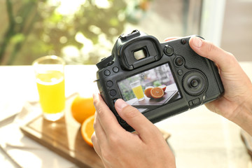 Female photographer taking picture of juice and oranges with professional camera, closeup