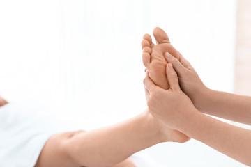 Woman receiving foot massage in wellness center, closeup