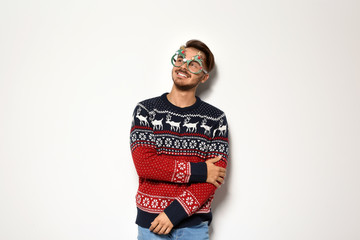 Young man in Christmas sweater with party glasses on white background