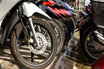 Motorcycles standing in the row. Row of many motorcycle wheel at the Showroom for sale.