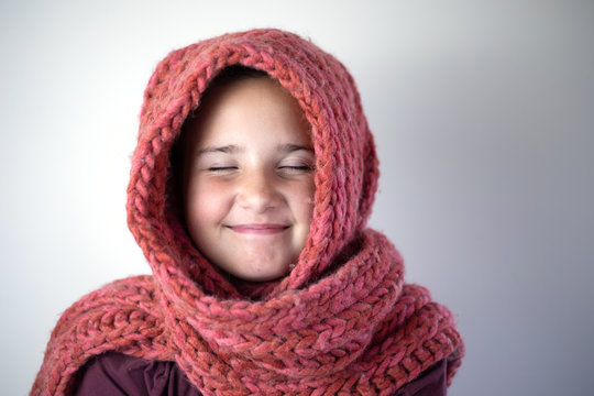 Young girl bundled with pink knitted scarf.
