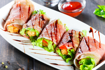 Fried meat wrapped in a prosciutto with tomatoes on wooden background. Hot Meat Dishes. Top view