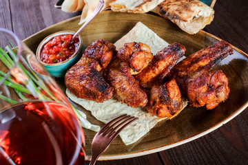 Grilled chicken wings, tomato sauce, greens and glass of wine on a plate. Hot Meat Dishes
