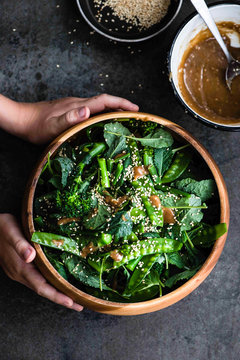 Person holding bowl with green salad sprinkled with sesame
