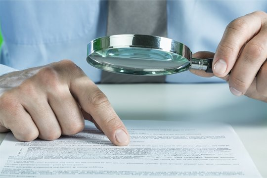 Businesswoman Holding Magnifying Glass, close-up view