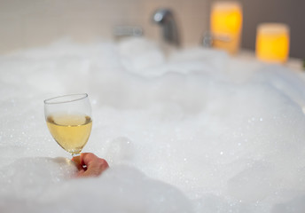 woman holding a glass of wine in bubble bath with candles