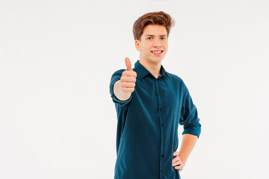Attractive smiling boy 18 years old student showing thumbs up on
