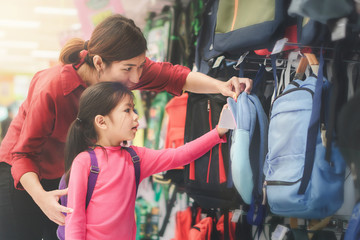 Back to school concept, Young asian mother or parent and little girl kid or cute pupil buying school satchel or bag in store, Selective focus