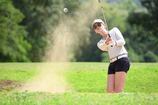 Asian woman golfer hitting a bunker shot