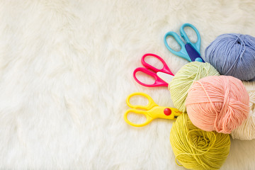Multicolored balls of yarn and scissors. Materials for creativity and crafts.Concept of a woman's hobby. Knitting and work at home.