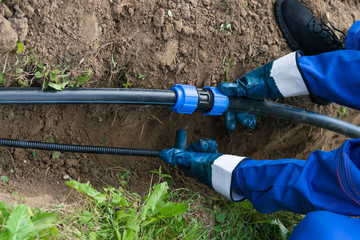 worker's hands hold a black pipe over a dug hole in the ground