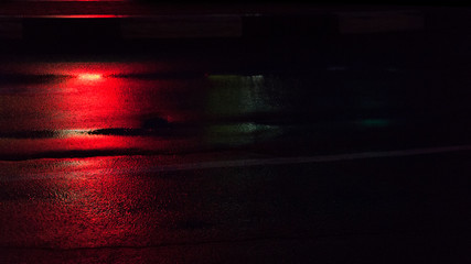 Background of wet asphalt with neon light. Blurred background, night lights of a big city, reflection, puddles. Dark neon bokeh.