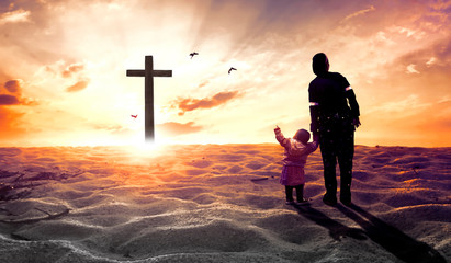 Worship concept: mother with children in front of the cross
