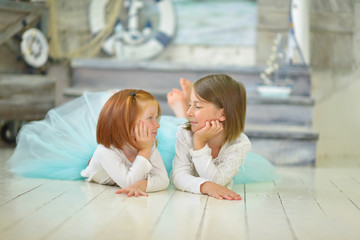 Cute little girls are laying on wooden beach in studio with sea scene