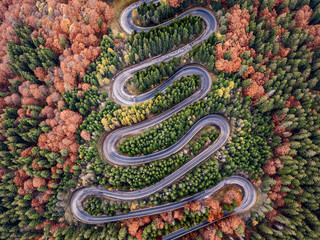 Winding road from high mountain pass, in autumn season.