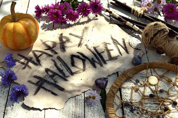 Shabby paper with text Happy Halloween, voodoo doll, pumpkin and last autumn flowers. Mystic background with ritual objects, occult, fortune telling and halloween concept