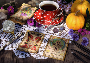 Still life with cup of tea, pumpkins, crystal, black candles and tarot cards on lace. Mystic background with ritual objects, occult, fortune telling and halloween concept