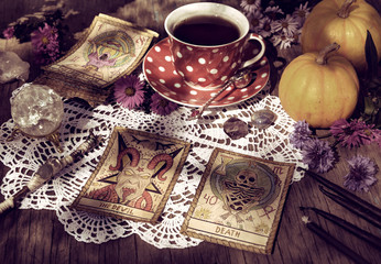 Fortune telling ritual with the tarot cards, pumpkins and cup of tea. Mystic background with ritual objects, occult, fortune telling and halloween concept