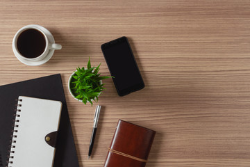 Notepad, coffee and mobile phone on wood background. Home business office supply.