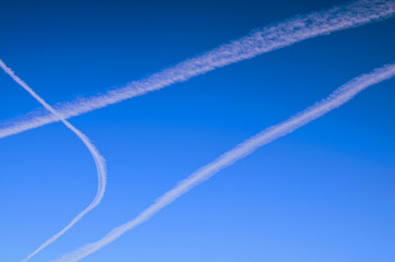 Condensation trails of planes in the sky. Sunny autumn blue sky. Aviation. Travel concept