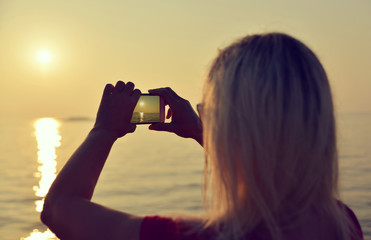 Woman with a mobile phone takes pictures of the sea with setting sun.