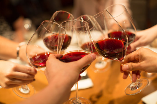 Group of Friends Celebrating Toasting Wine Glasses. Business Meeting Cheers. Symbol of Friendship or Family Celebration. Fine Dining at Luxury Restaurant.  Red Wine in Glasses. Diverse People.