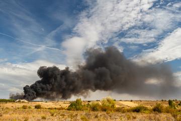 Contaminación. Incendio en una planta de reciclaje y columna de humo.