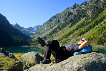 Tourist resting at Gaube lake. Hautes Pyrenees, France.