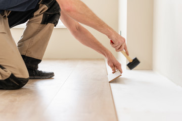 Strikes with a soft hammer on the part with a lock, for fixing. Installing laminate flooring fitting the next piece - focus on hand. Man laying laminate flooring